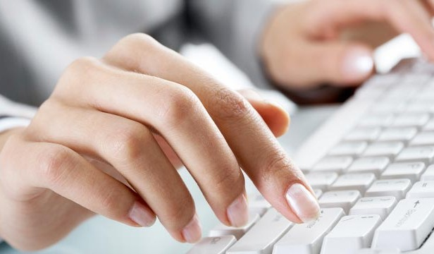 Image of a woman's hands on a computer keyboard