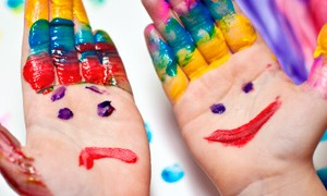 Image of a child's hands painted with a smiley face and a sad face