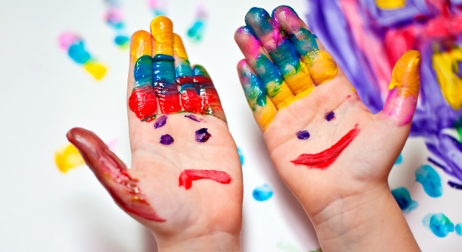 Image of child's hands painted with a sad face and a smiley face